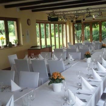 Mniejsza sala z przystrojonymi stołami na imprezę okolicznościową